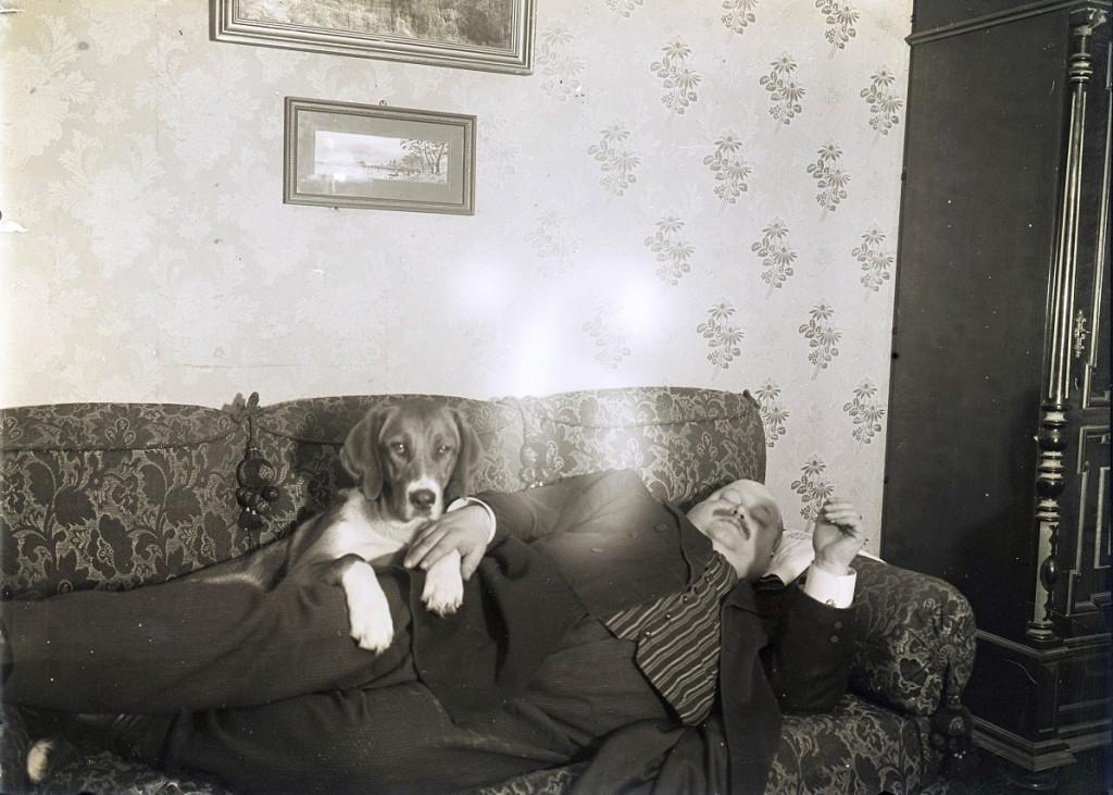 Julius Hirn sohvalla koira seuranaan 1900-luvun alkupuolella.